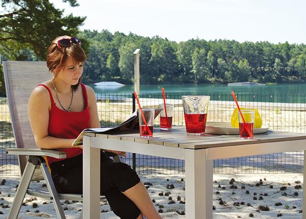 Junge Frau sitzt auf der Terrasse vom Ferienhaus Bernsteinsee