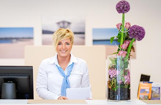 Lächelnde Empfangsmitarbeiterin an der Rezeption