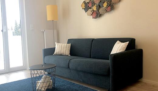 Sofa mit Beistelltisch und Zugang zum Balkon