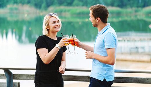 Paar feiert mit Cocktails auf der Seeterrasse